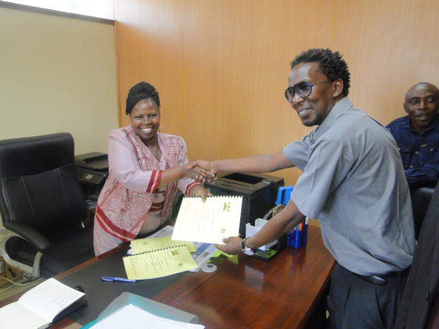 Jack Makau of the Kenya SDI Alliance and Hon. Esther Njuguna of Kiambu County Government exchange signed copies of the MOU.